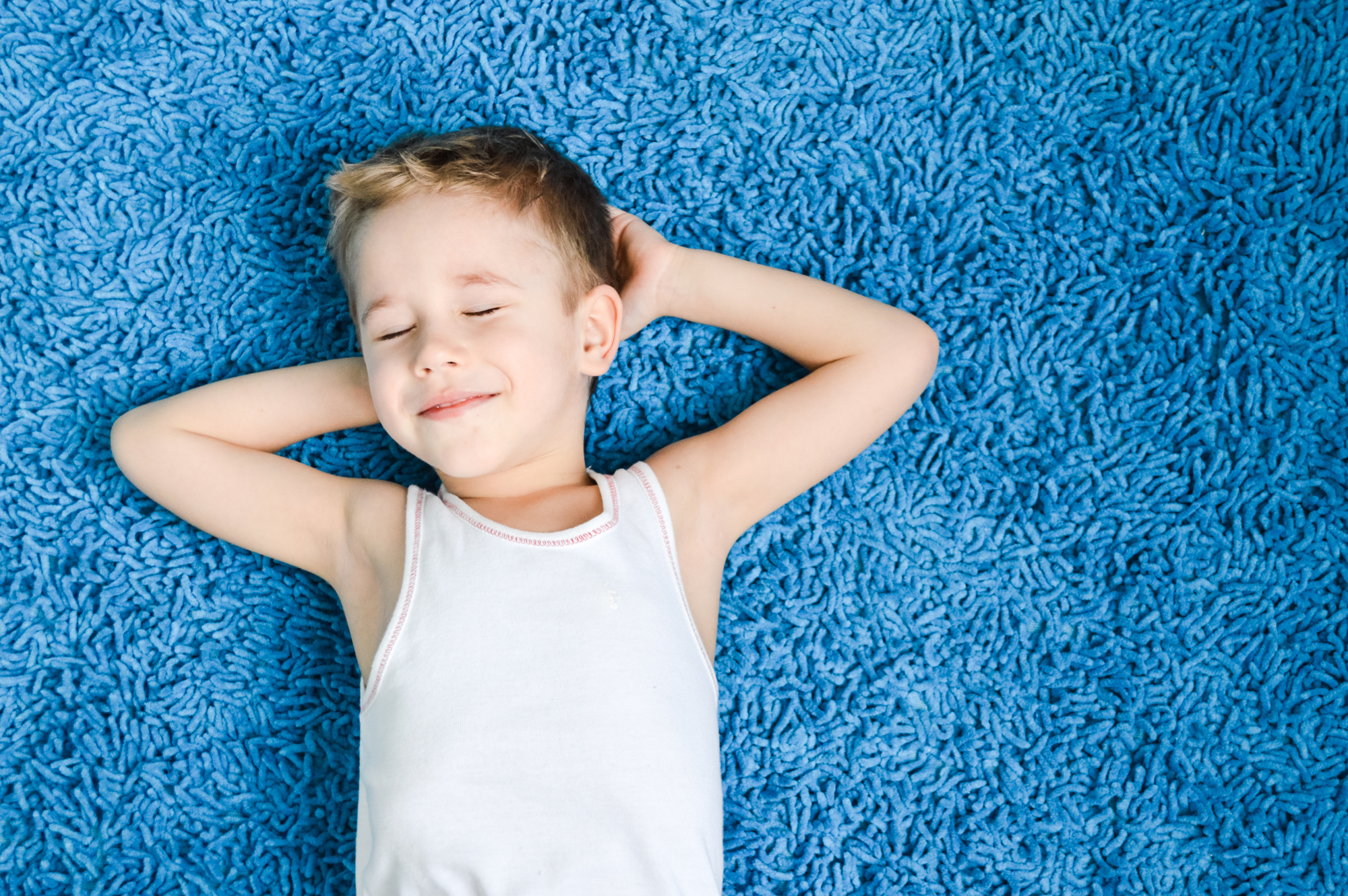 Happy boy smiling kid on blue carpet in living room at home
